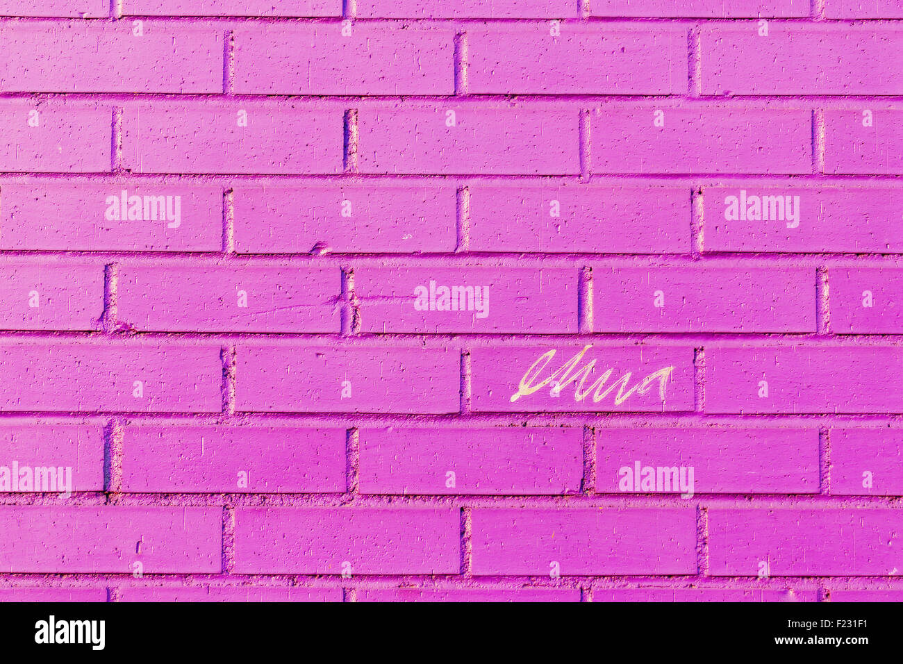 scribble on a pink bricked wall - Stock Image