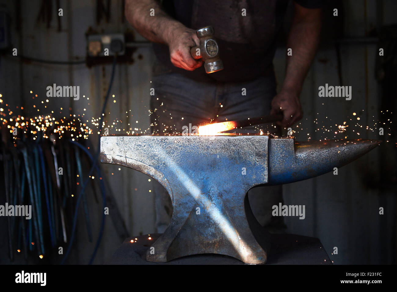 A blacksmith shaping a hot piece of iron on an anvil with a hammer, with sparks flying. - Stock Image