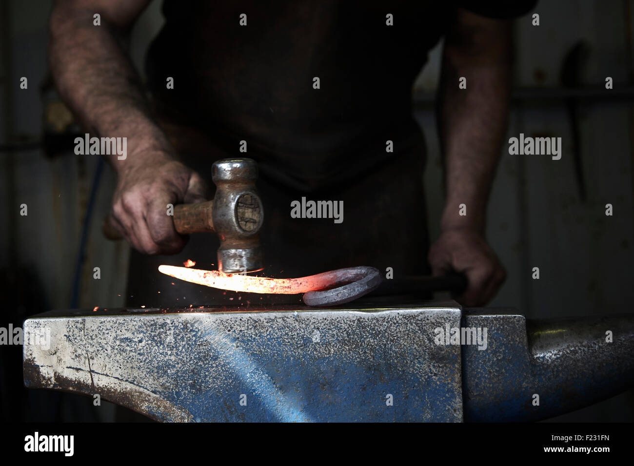 A blacksmith shaping a hot piece of iron on an anvil using a hammer. - Stock Image