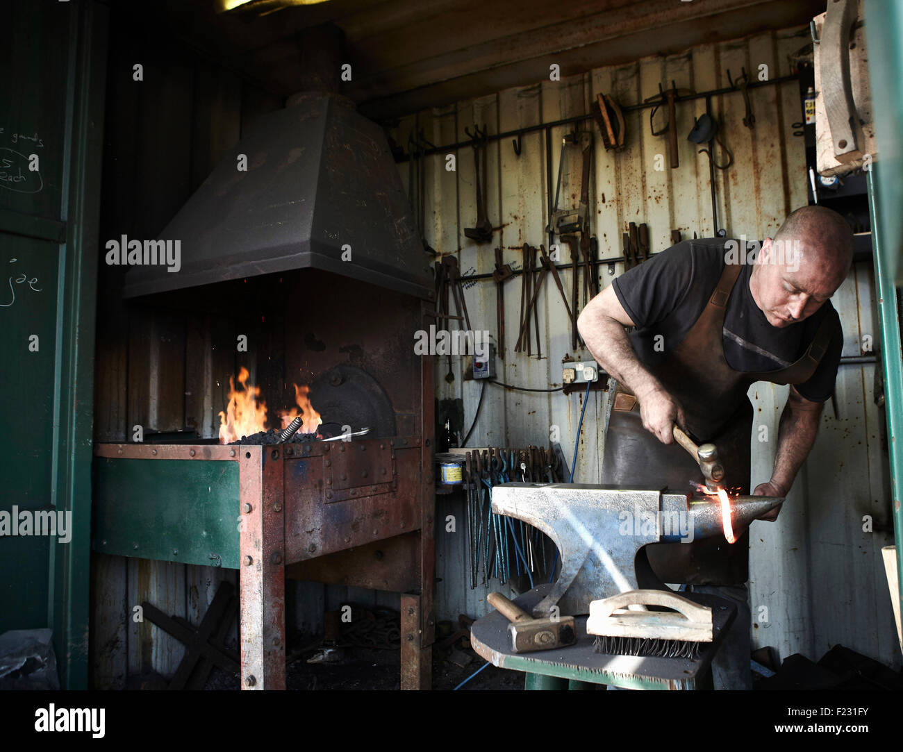 Blacksmith shaping a hot piece of iron on an anvil in a traditional forge with an open fire. - Stock Image