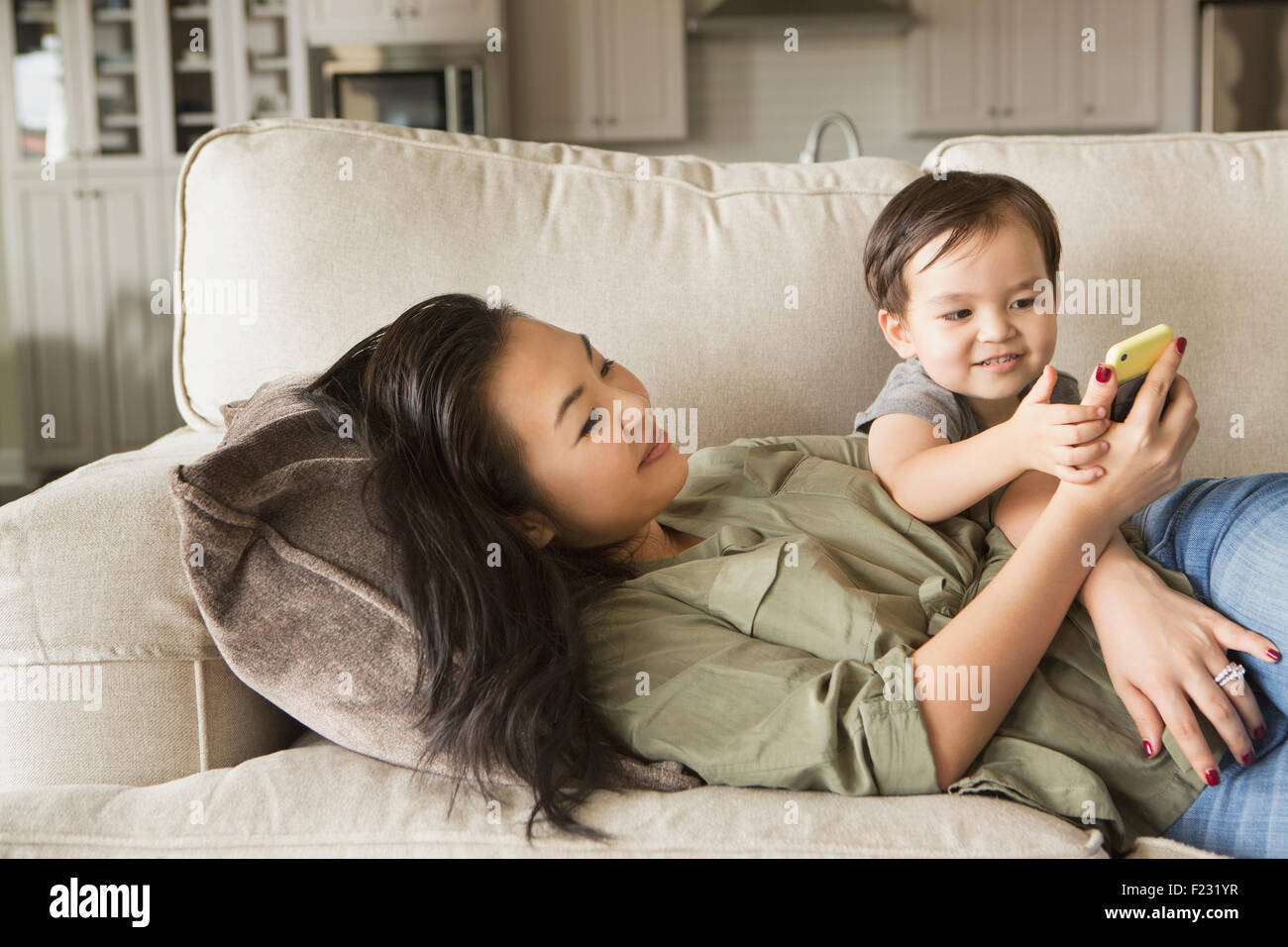 Woman lying on a sofa, smiling, cuddling with her young son and looking at a cell phone. Stock Photo