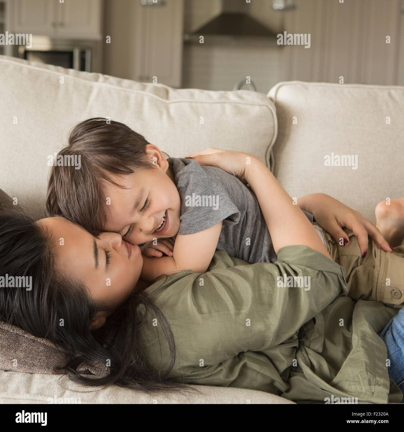 A woman lying on a sofa, smiling, cuddling her young son. Stock Photo