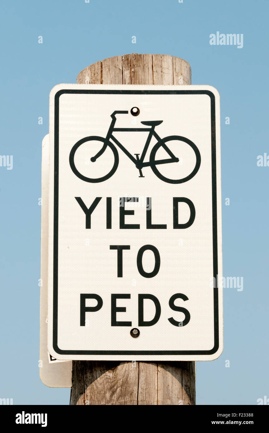 A sign tells cyclists to give way to pedestrians. - Stock Image
