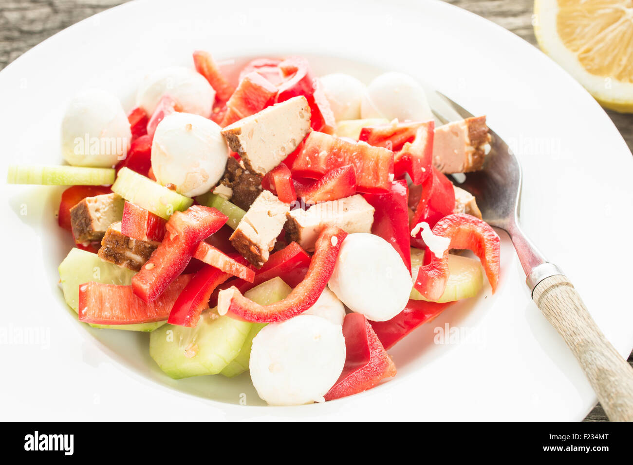 Salad with tofu and vegetables on a plate with fork - Stock Image