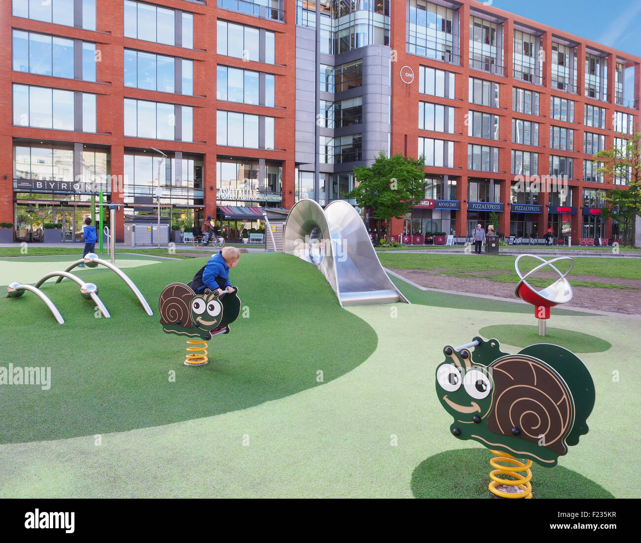 The childrens playgound with the shops behind in Piccadilly Gardens, Manchester, UK. - Stock Image