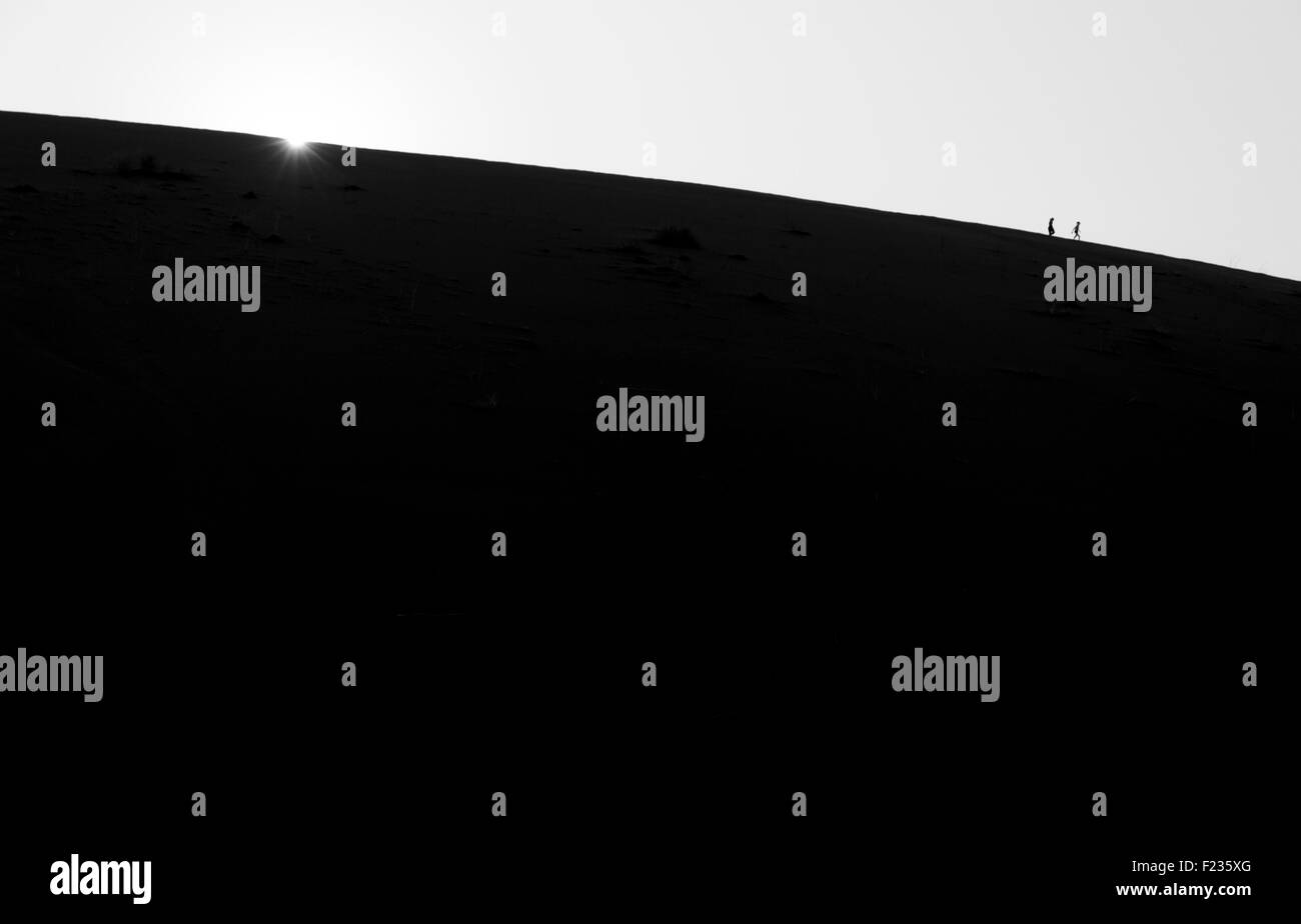 Sun rising over sand dune with silhouetted figures - Stock Image