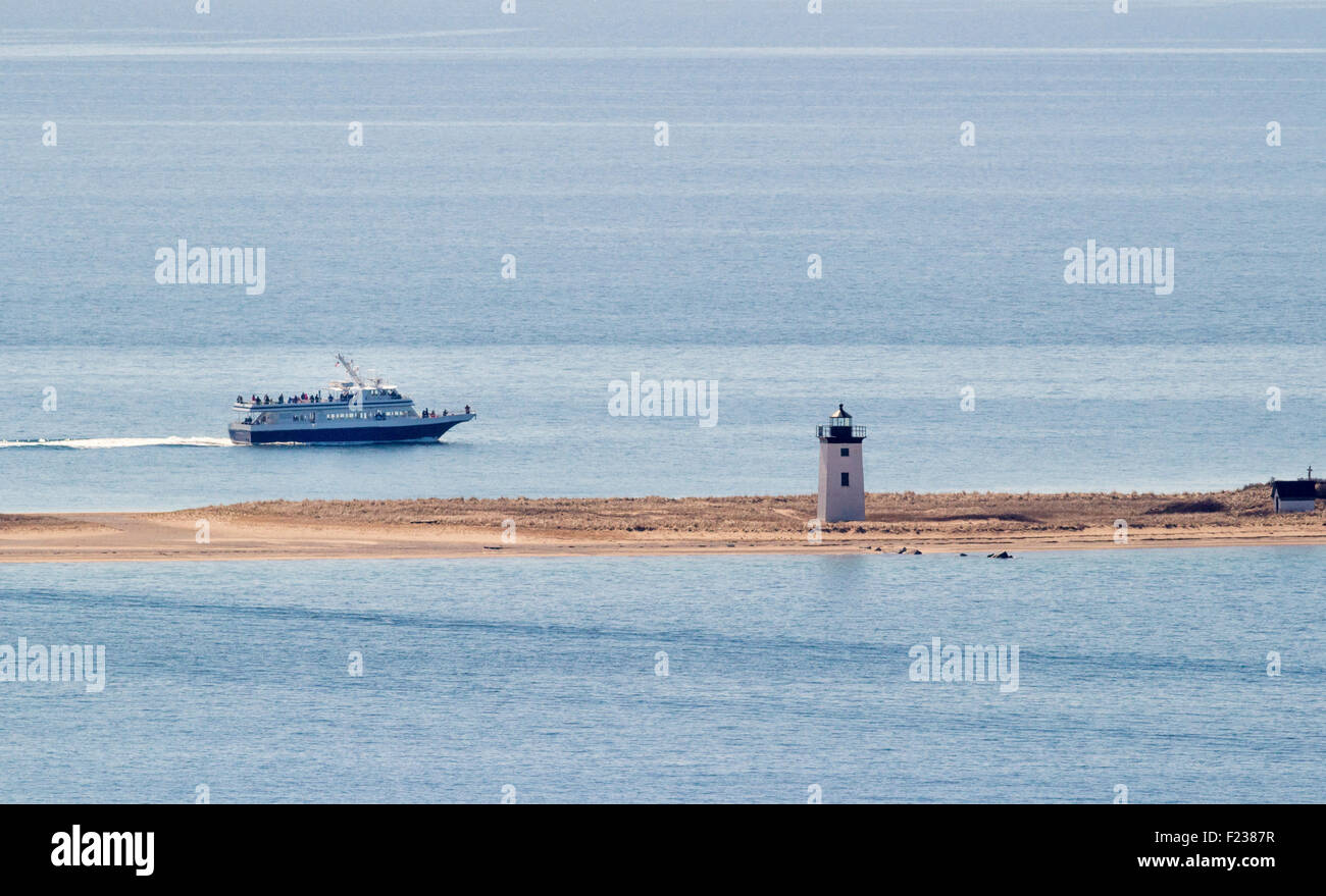 A whale watch boat traveling past a lighthouse to see the whales. - Stock Image