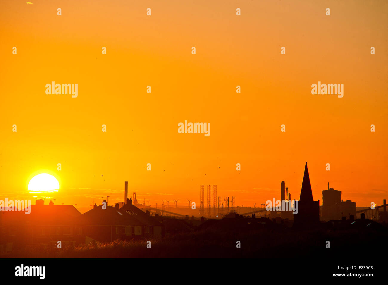 sun sets over Redcar SSI Steelworks industry silouetted against an orange glow - Stock Image