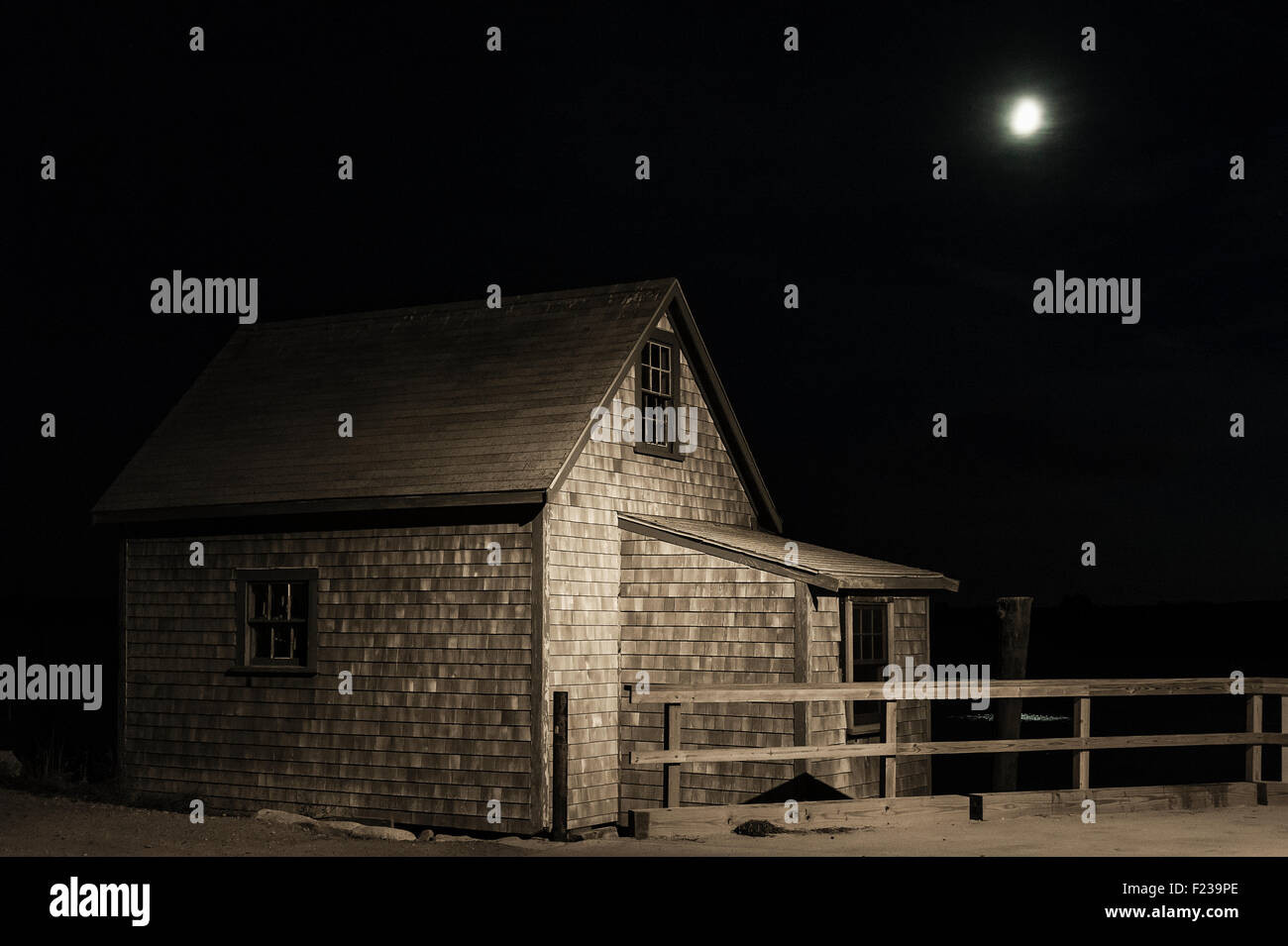 Full moon shines on moody coastal shanty. - Stock Image