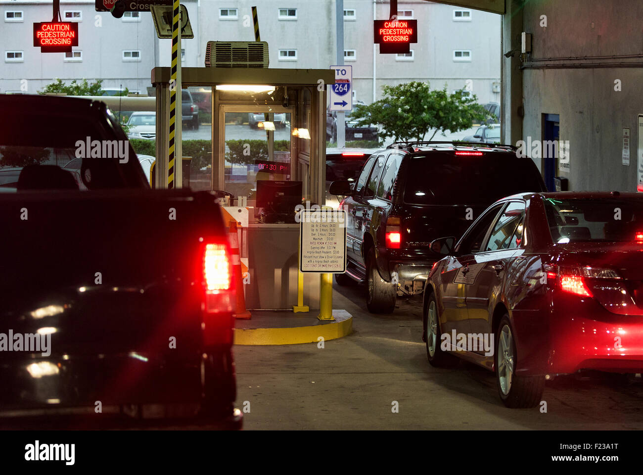 Cars wait to pay fee at a parking garage exit. Stock Photo