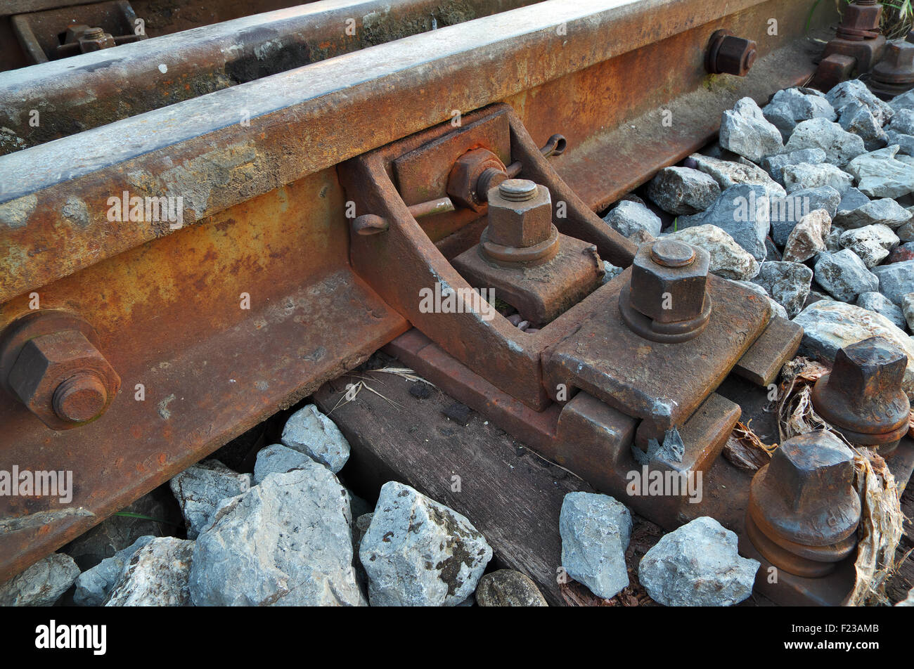 Rusty bolts and screws on a railroad track Stock Photo