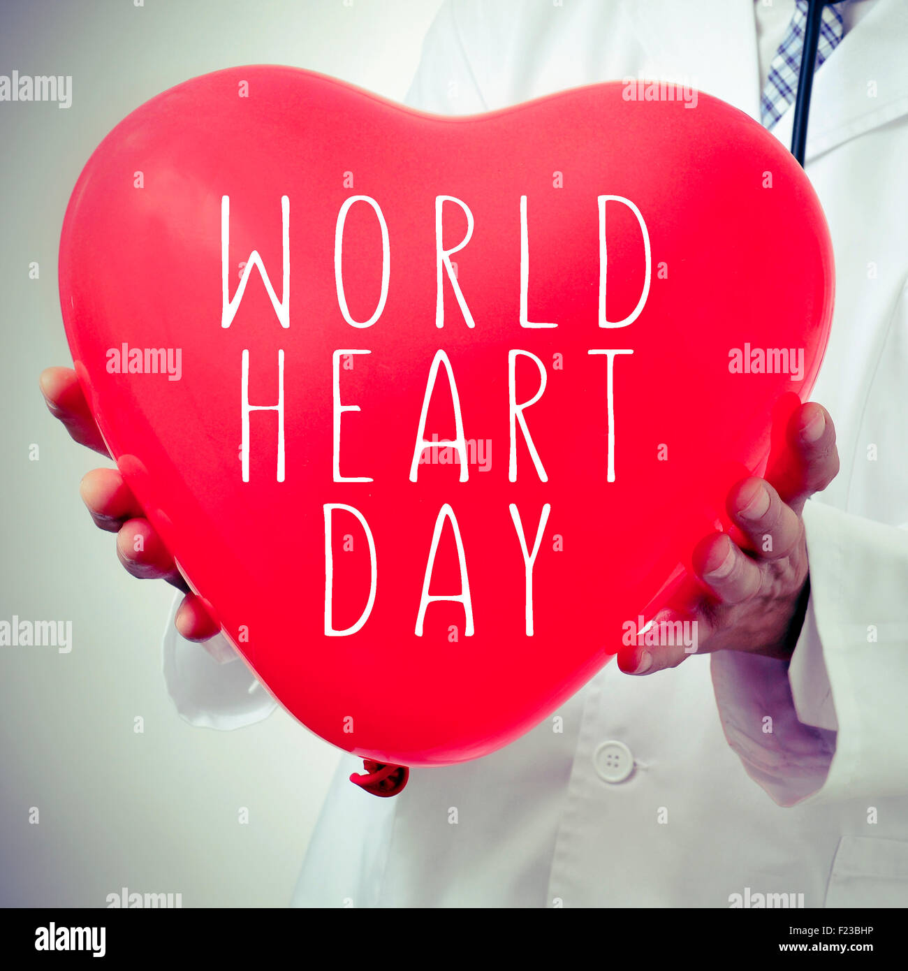 closeup of a doctor man showing a red heart-shaped balloon with the text world heart day written in it - Stock Image