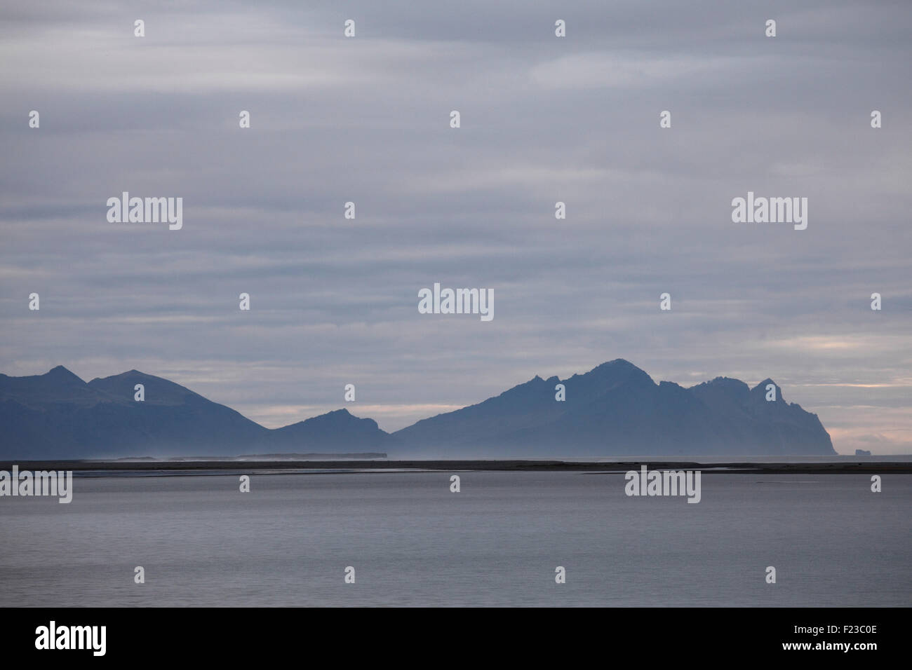 Mountains by the coast at Hof in south-east Iceland. The North Atlantic lies beyond a thin peninsula of land. - Stock Image