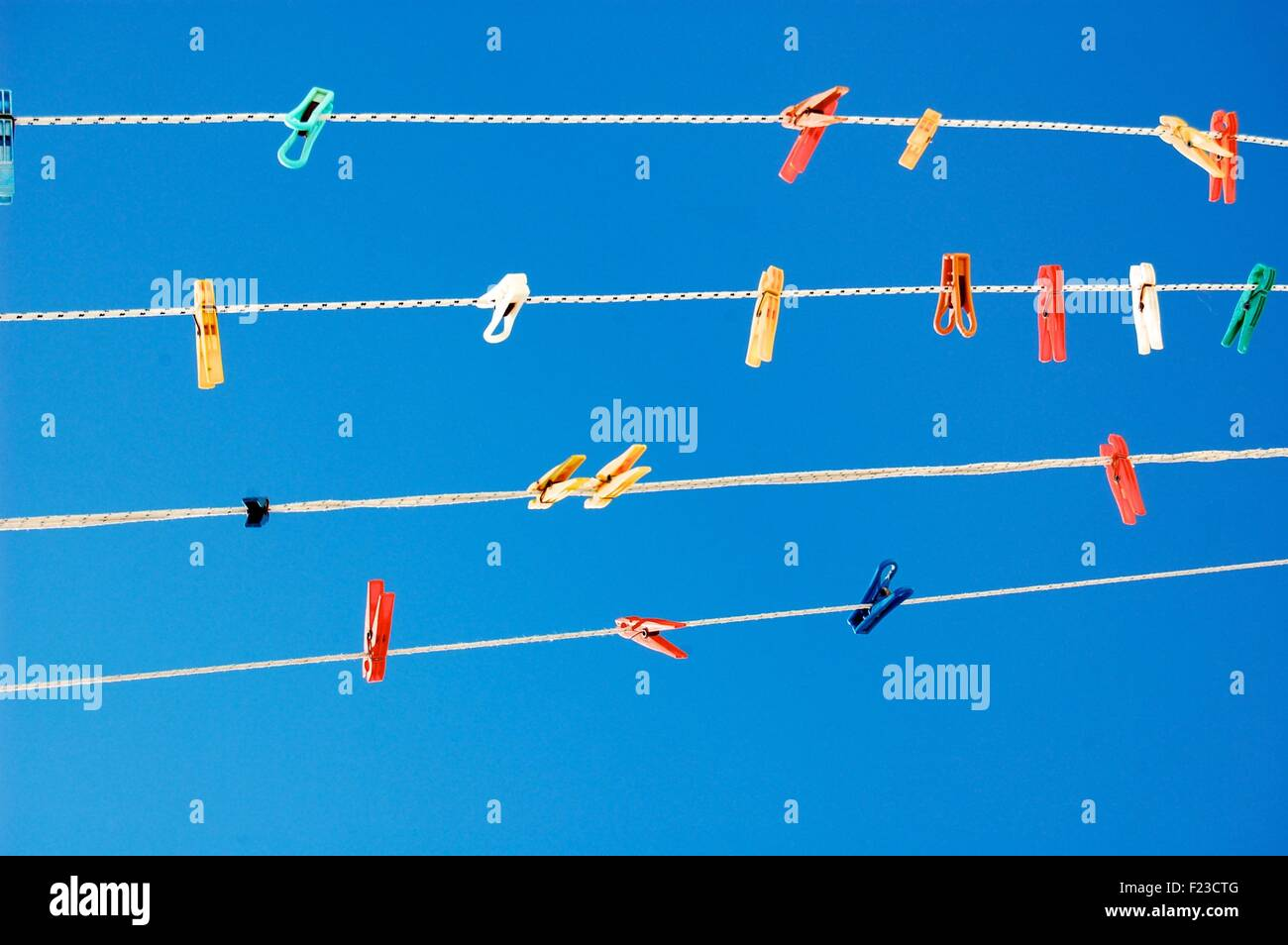 Multicolored pegs on washing lines against a bright blue sky - Stock Image