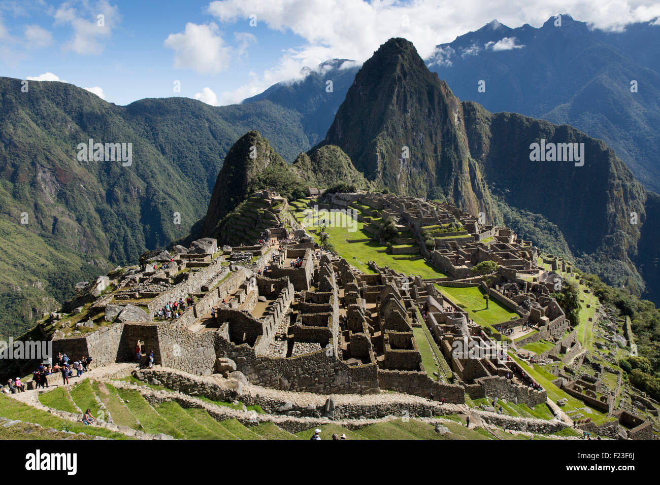 Peru, Morning sun lights Inca ruins at Machu Picchu with Huayna Picchu peak rising above the Urubamba River Stock Photo