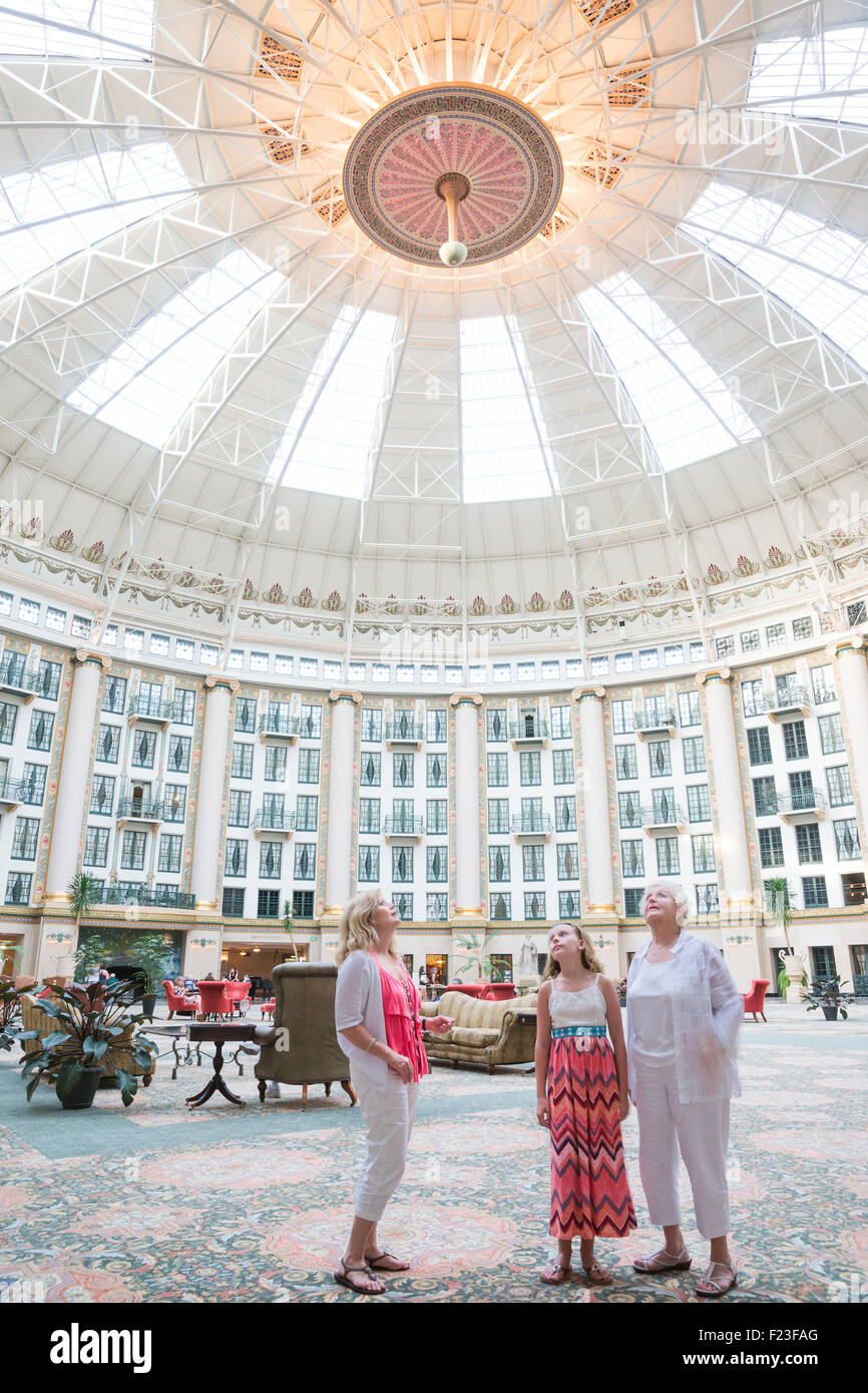 Caucasian multi-generational family look up at the domed ceiling in the six story atrium at West Baden Springs Resort - Stock Image
