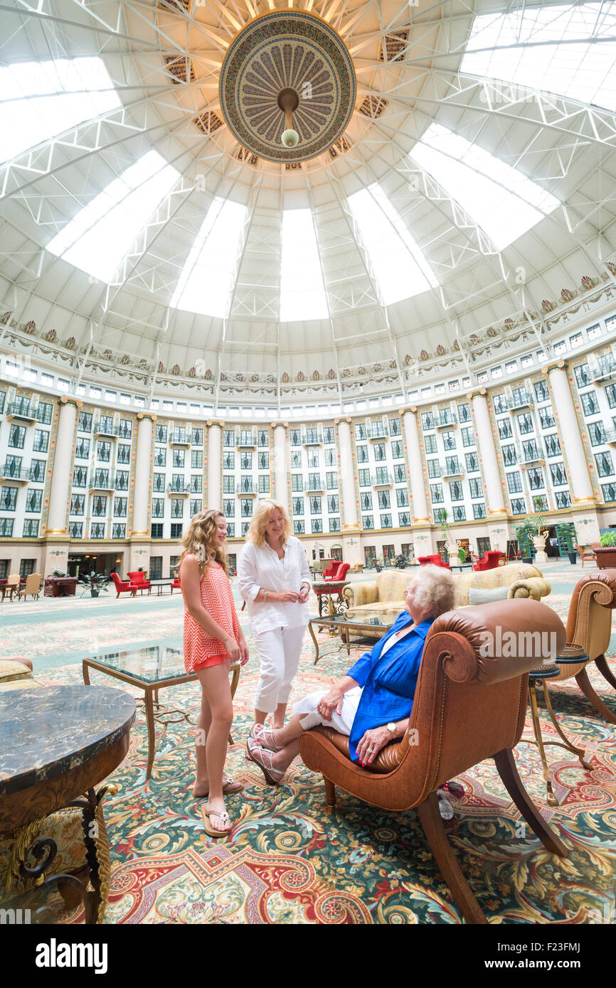 Caucasian multi-generational family converse in the domed six story atrium at West Baden Springs Resort, French - Stock Image