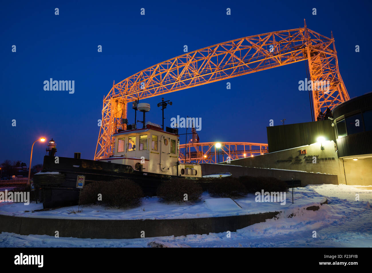 Illuminated Aerial bridge over Lake Superior with tug boat in foreground at dawn in winter, Duluth, Minnesota, USA - Stock Image
