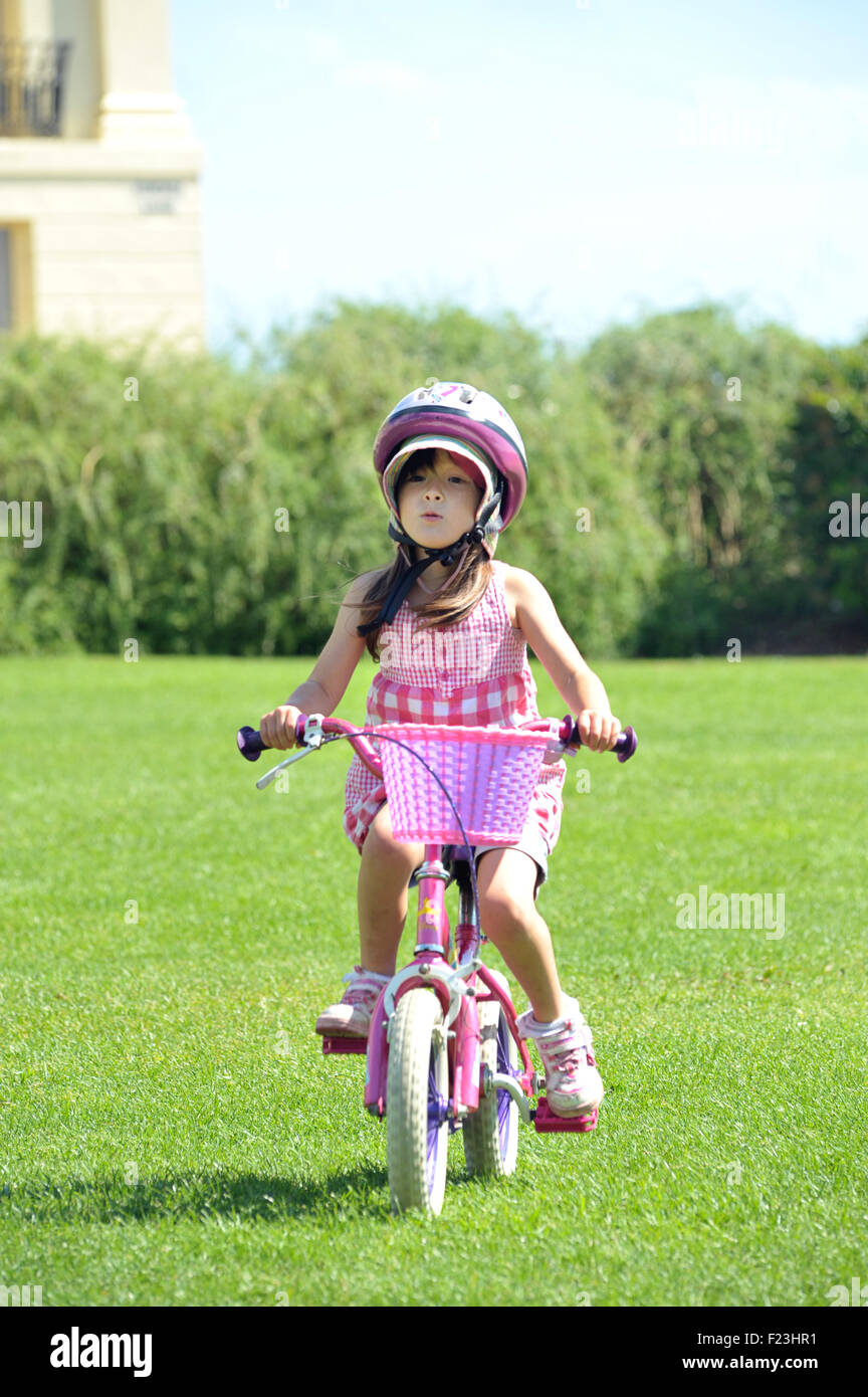 Girl riding a bicycle on grass with crash helmet. Sussex, England - Stock Image