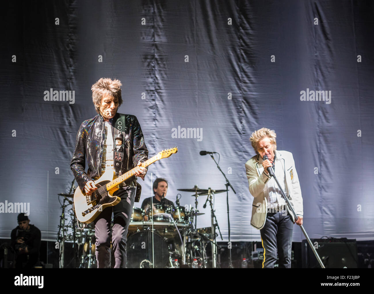 Rod Stewart sings Ronnie Wood smokes. The Faces reunited perform in concert live on stage together in Surrey, in - Stock Image
