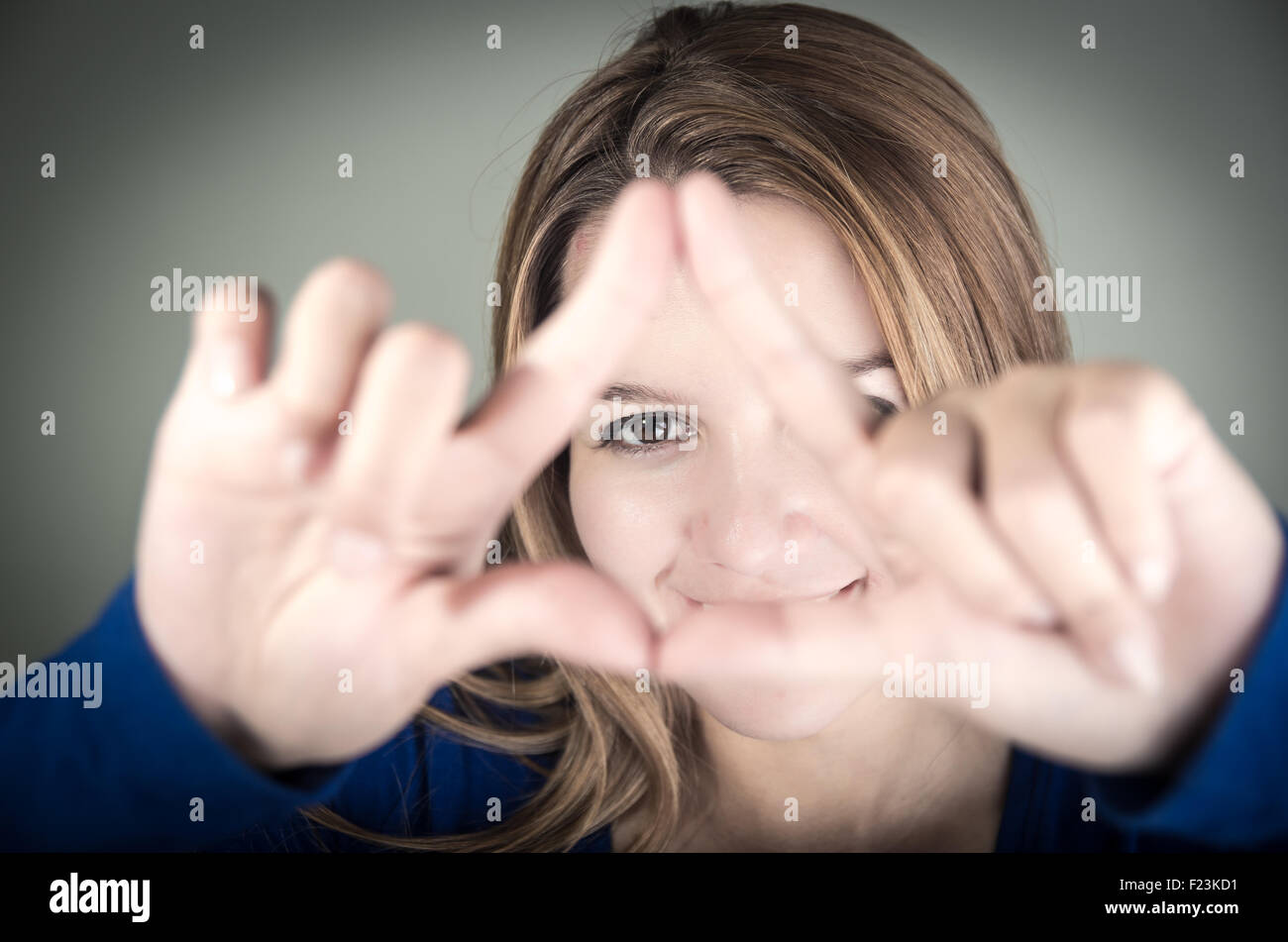 Closeup Portrait Of Cute Young Teen Girl Making A Triangle With