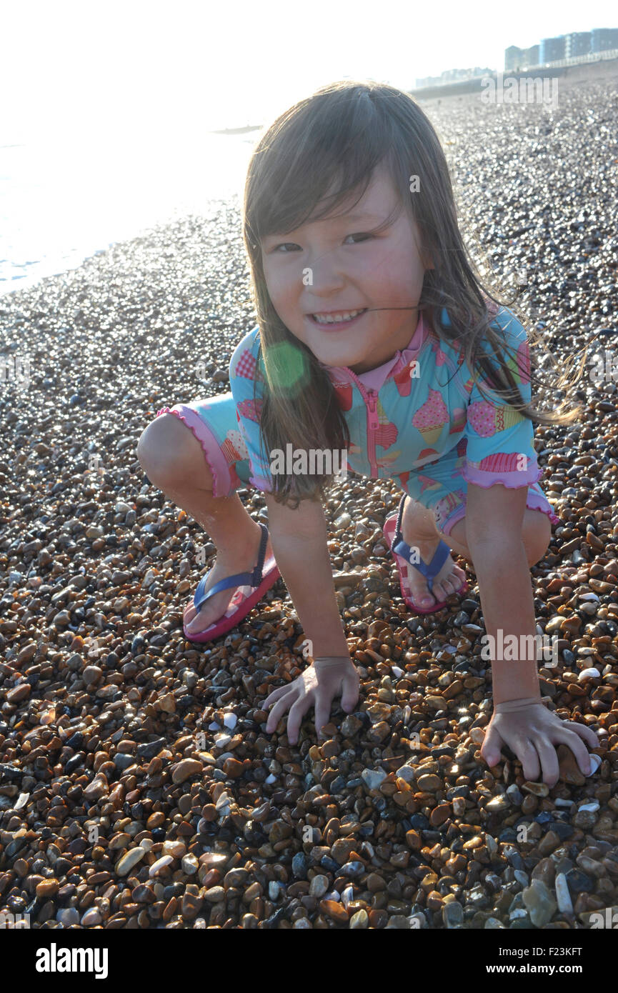 5 year old girl on the beach. Brighton, England. Model Released. - Stock Image