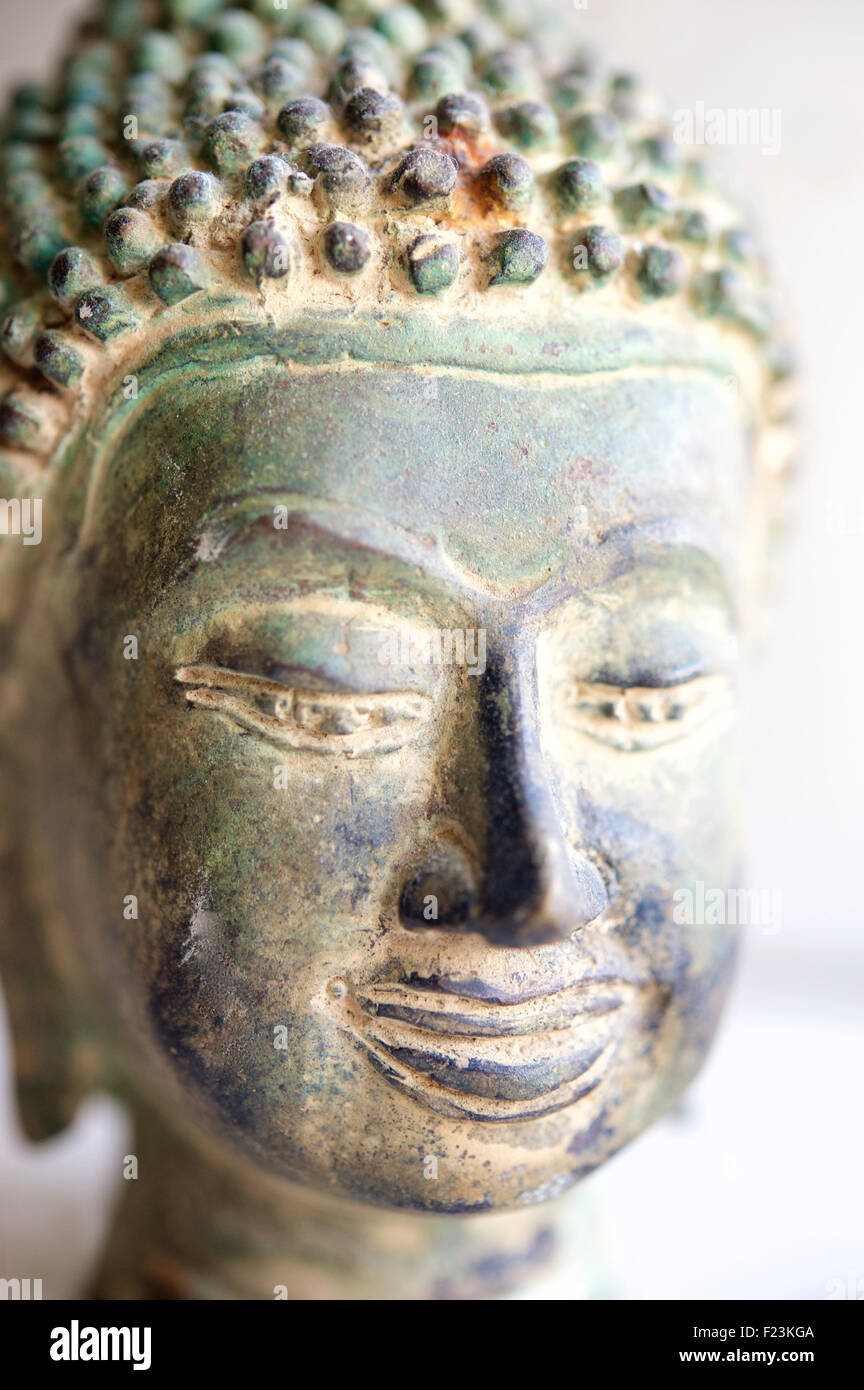Detail of a cast brass buddha head with a weathered patina that looks like bronze. From Thailand - Stock Image