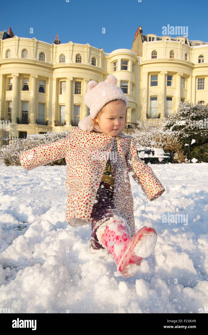 Toddler aged 2-3 stomping around in the snow, Brunswick Square, Brighton and Hove. MODEL RELEASED - Stock Image