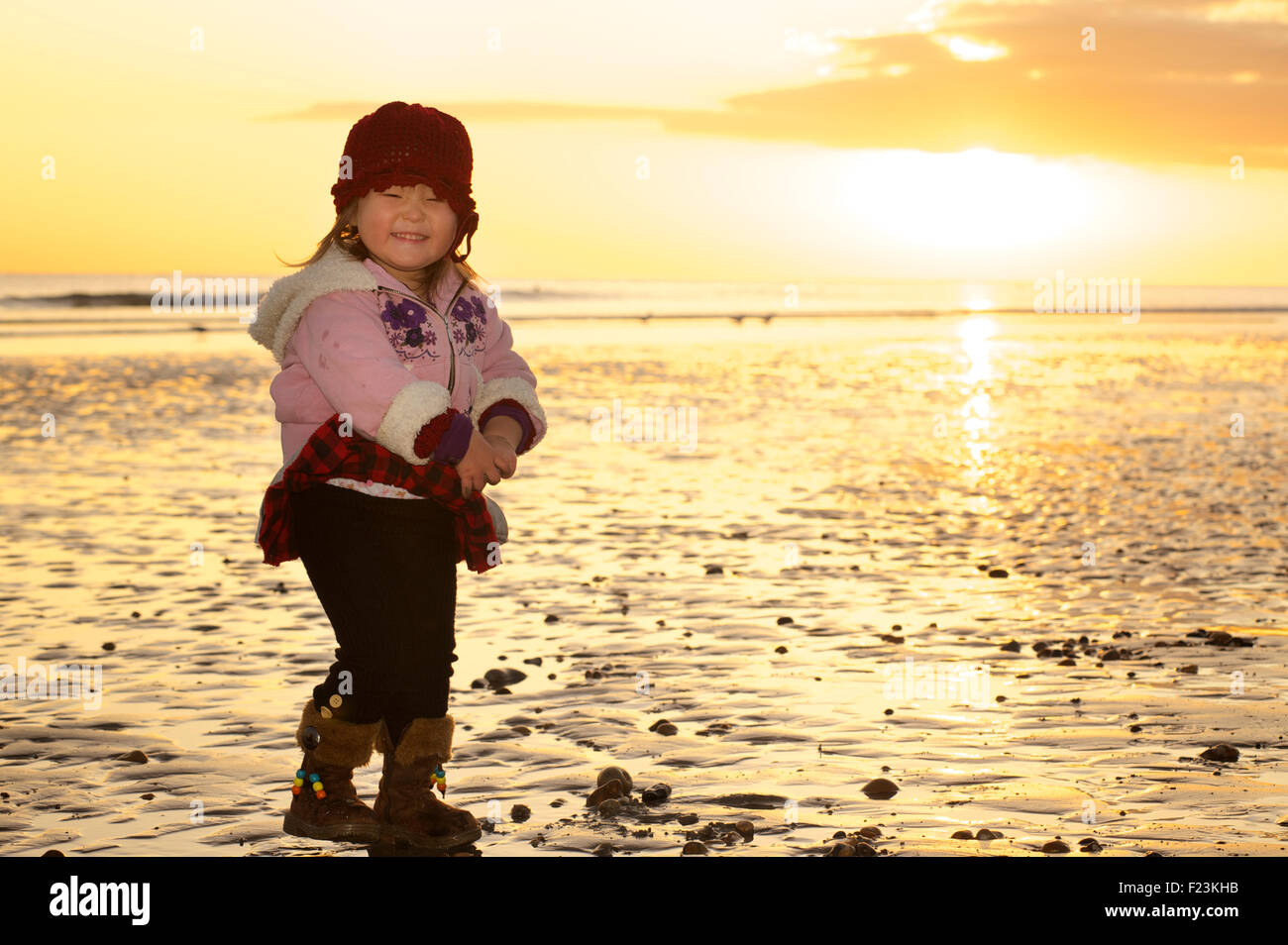 Toddler on the beach in the sand at low tide. MODEL RELEASED - Stock Image