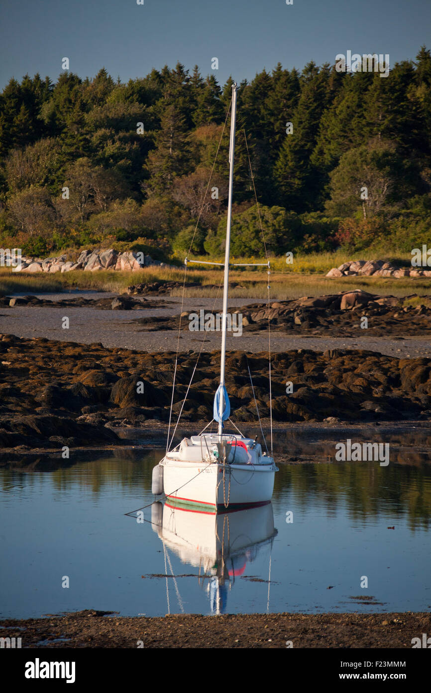 Lonely Sailboat anchored in Cape Porpoise Harbor at low tide - Stock Image