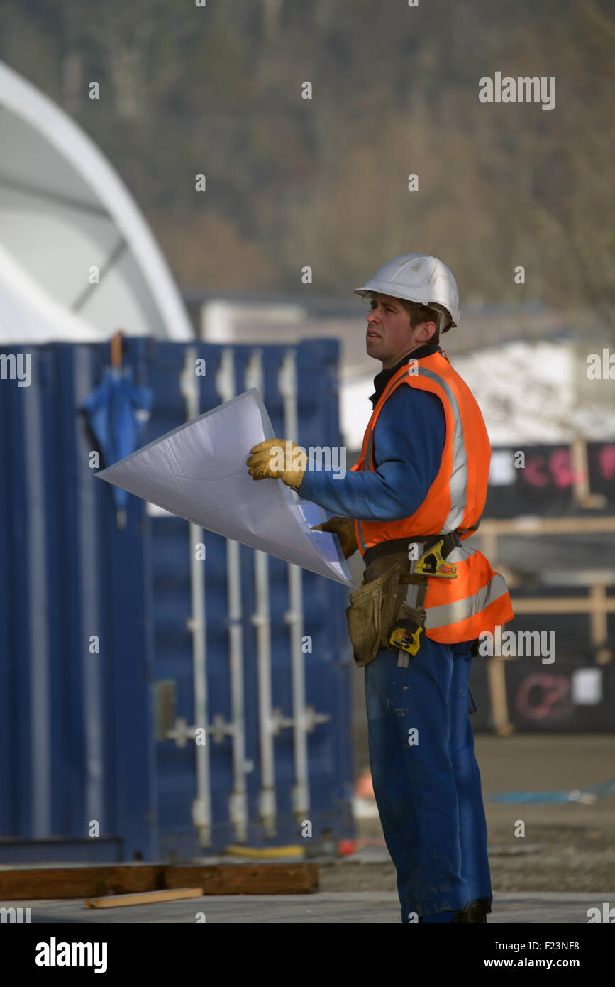 A builder consults his plans at the construction site Stock Photo