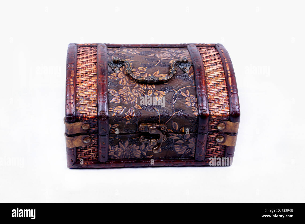 An ancient wooden box with beautiful carvings used for storing jewelery, isolated on a white background. - Stock Image