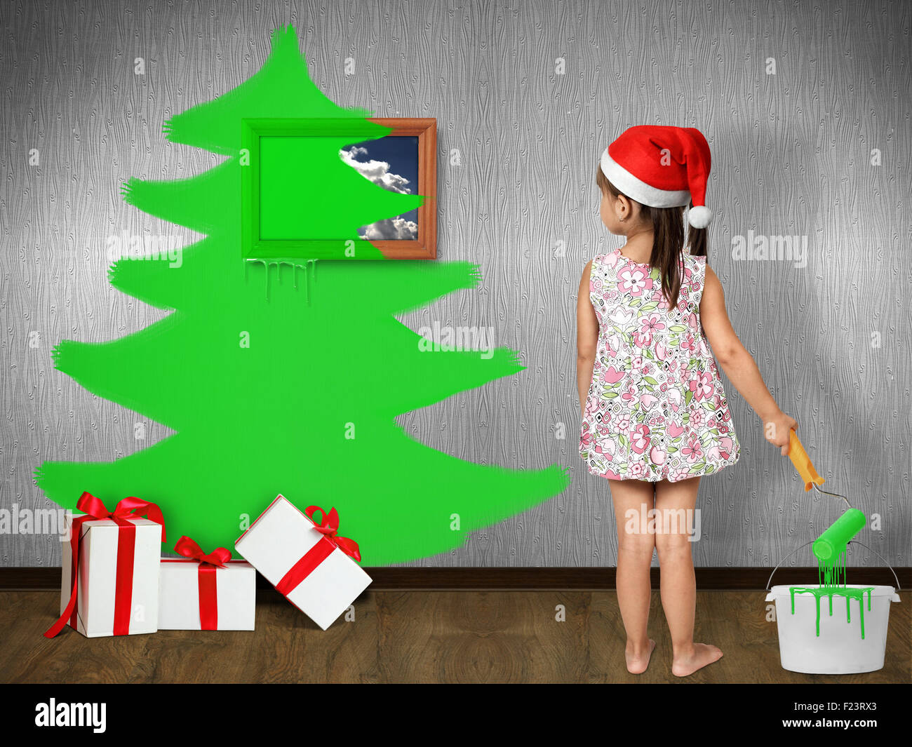 Funny child dressed Santa hat, draws Christmas tree on wall at home, xmas concept - Stock Image