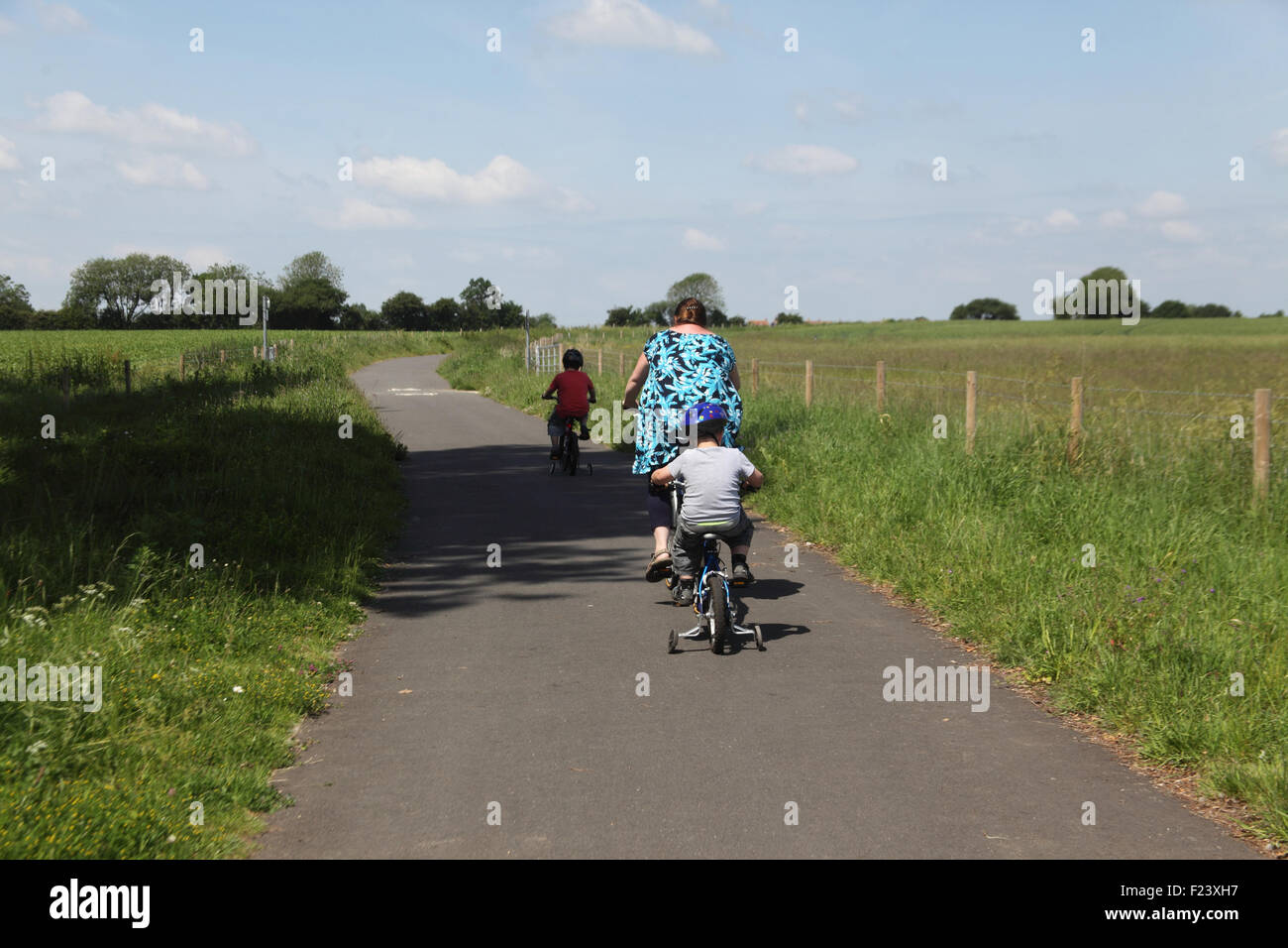 Mother and children riding bikes on cycle path from Watton to Griston Norfolk - Stock Image
