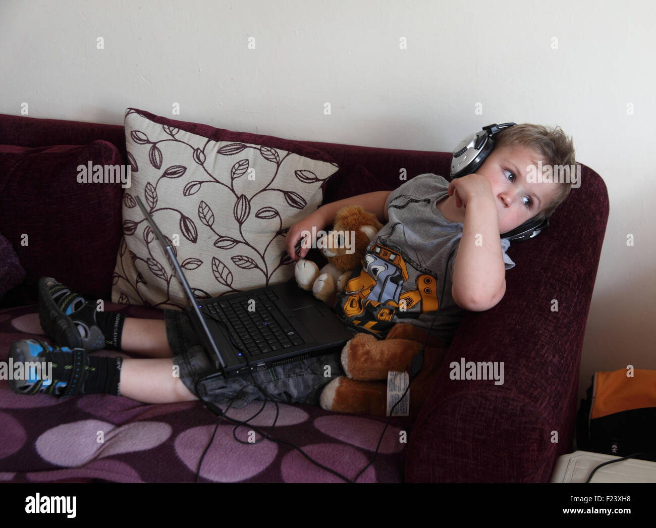 Small boy watching vidoes on laptop computer - Stock Image