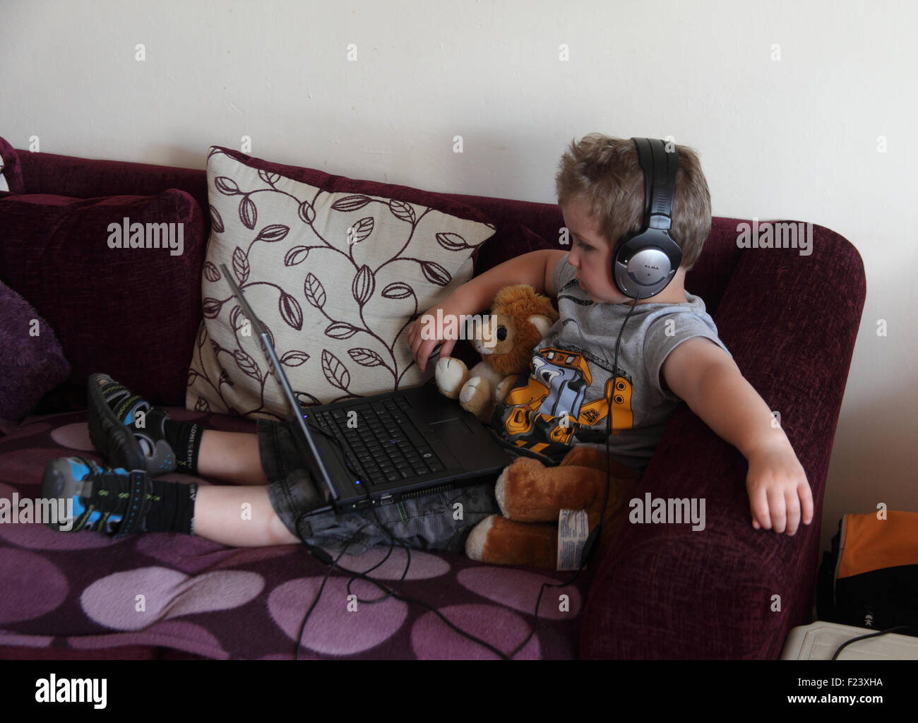 Small boy using laptop computer and headphones - Stock Image