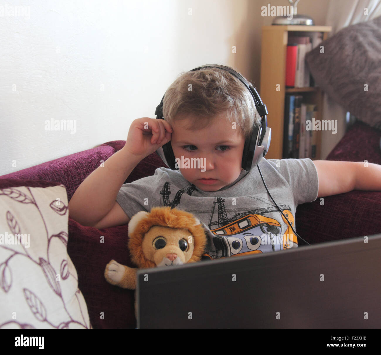 Small boy using laptop computer with headphones - Stock Image