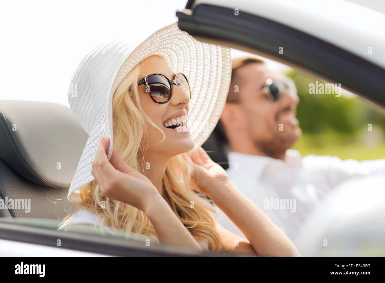 happy man and woman driving in cabriolet car - Stock Image