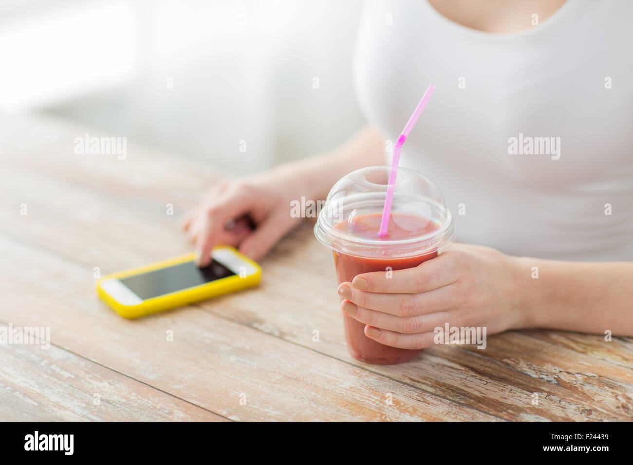 close up of woman with smartphone and smoothie - Stock Image