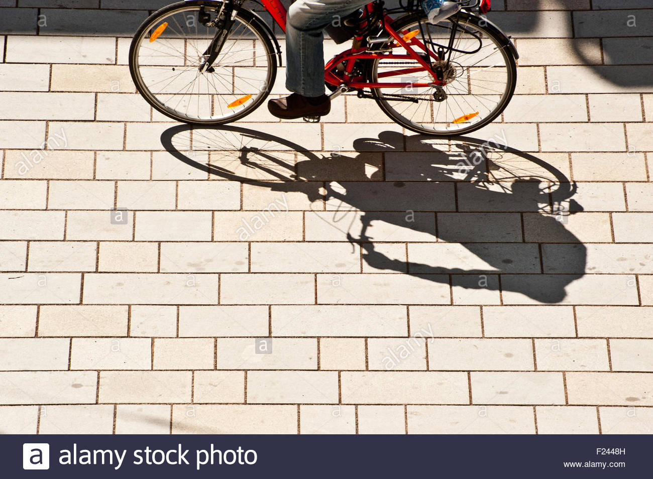 man in bicycle projecting a shadow on the street - Stock Image