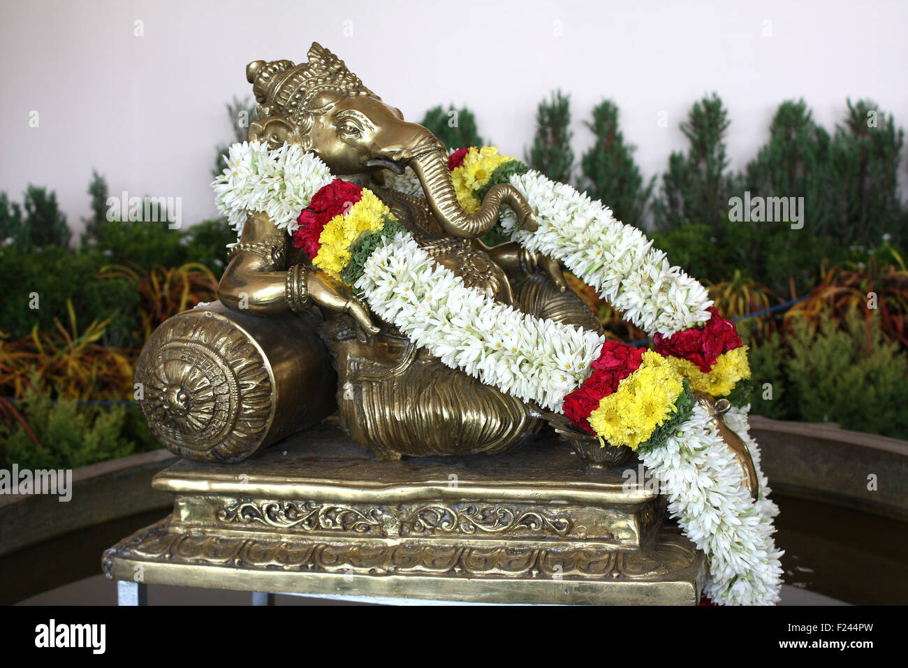 A metallic idol of lord Ganesha with flowers garland. - Stock Image