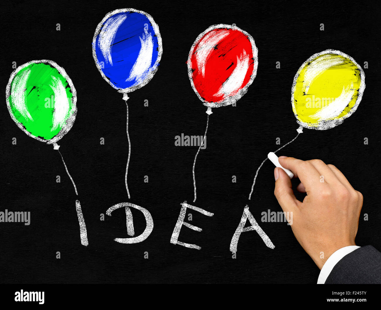 Man writing the word 'Idea' with balloons attached to it with chalk on blackboard background - Stock Image