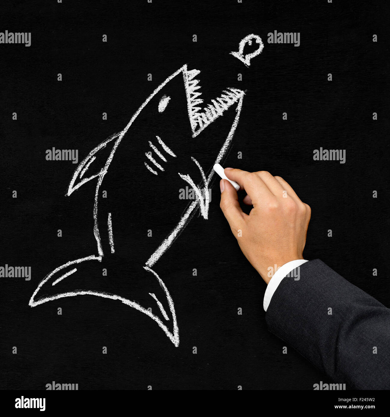 Businessman drawing shark hunting little fish with chalk on blackboard - acquisition, challenge or danger concept - Stock Image