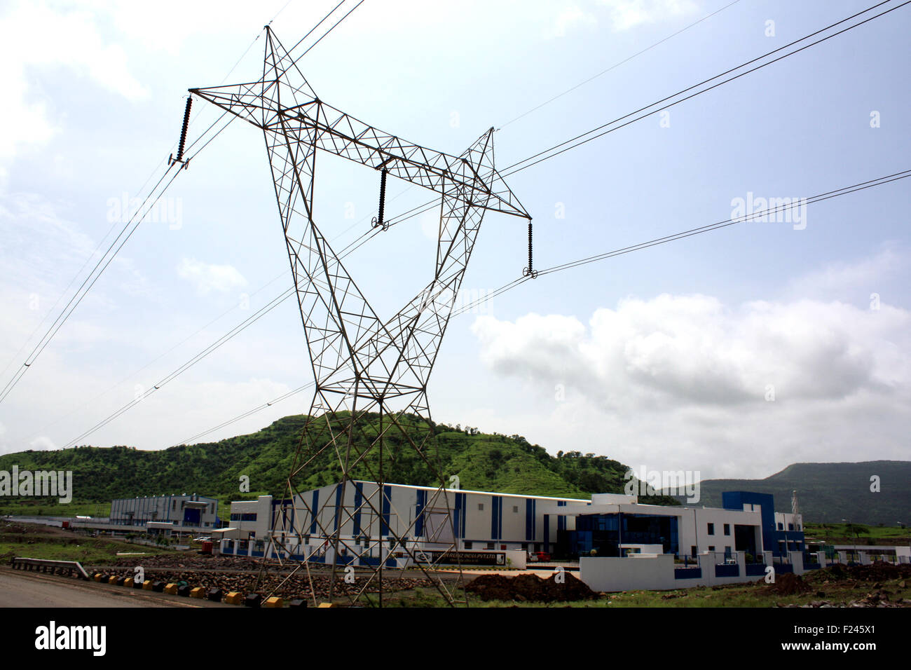 A tower of power cable lines leading to huge factories, in India. - Stock Image