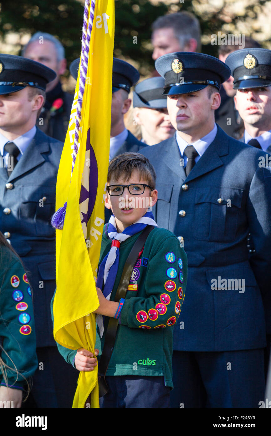 England, Rememberance Sunday. Young boy scout with glasses standing holding flag with uniformed soldiers behind - Stock Image