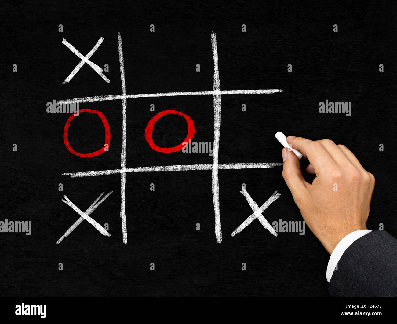 Man drawing tic-tac-toe game with chalk on blackboard background - Stock Image