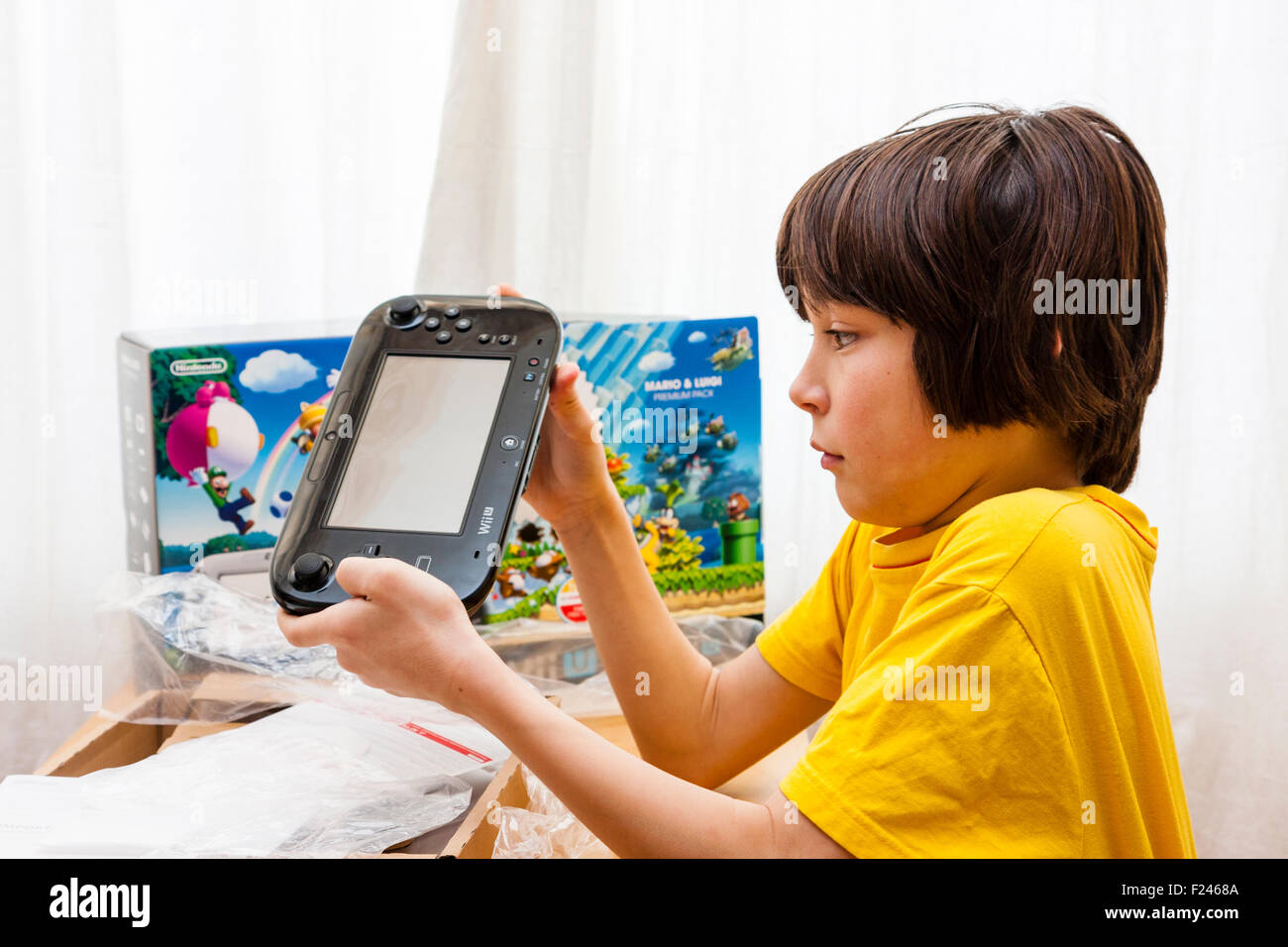 Caucasian child, tween, 10 to 12 years old, holding in both hands Nintendo Wii U gaming console, looking very pleased, - Stock Image
