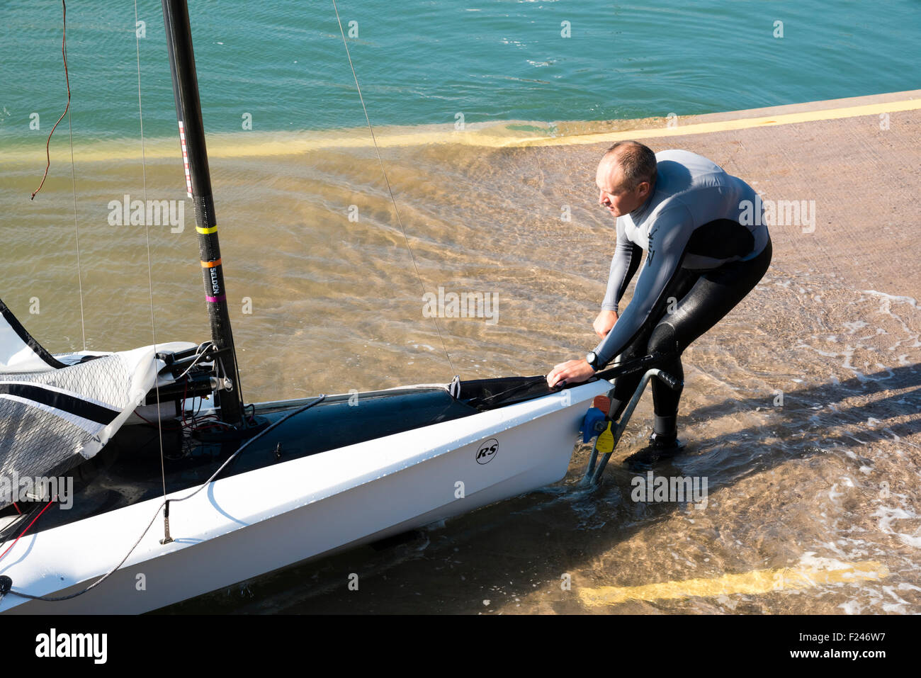 Sailing Dinghy being pulled up a slipway by a man wearing a wetsuit, UK. - Stock Image