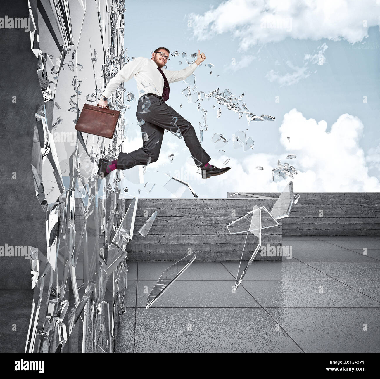 smiling businessman broke glass with jump - Stock Image