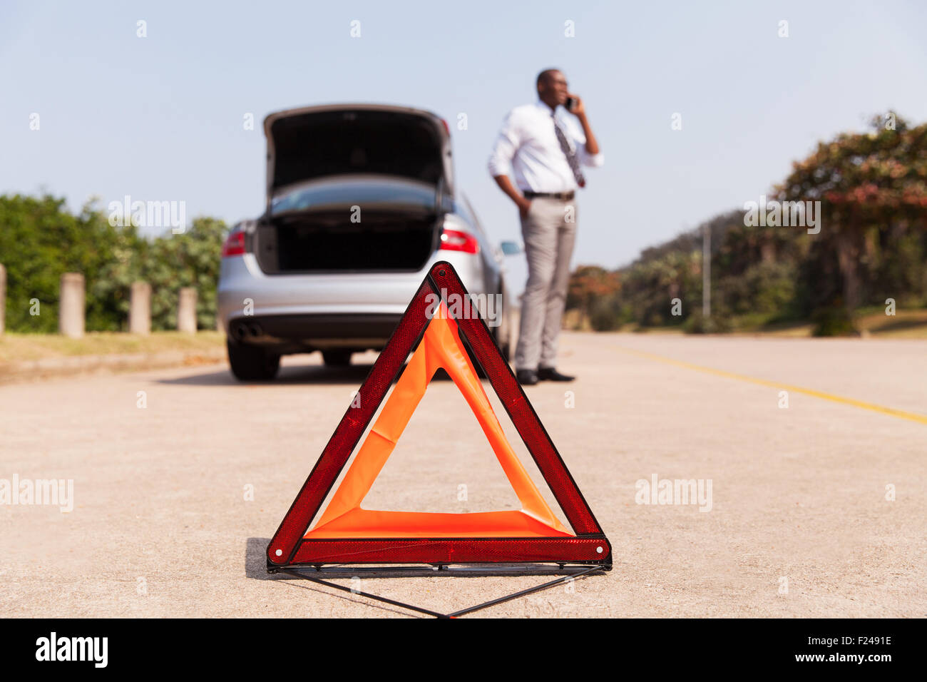 african male driver calling for help after car broke down by the